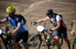 Competitors carry their bikes as they walk, during stage 6 of the 13th edition of the Titan Desert 2018 mountain biking race between Merzouga and Maadid on May 4, 2018.  The Titan Desert 2018 is a 600 kilometres mountain bike race completed over six days, snaking between Boumalne Dades, at the foot-slopes of the High Atlas summits, and Erfoud, an oasis town in the Sahara Desert. / AFP PHOTO / FRANCK FIFE