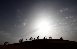 Competitors push their bikes up a sand dune during Stage 5 of the 13th edition of Titan Desert 2018 mountain biking race around Merzouga in Morocco on May 3, 2018.  The Titan Desert 2018 is 600 kilometre mountain bike race completed over six days, snaking between Boumalne Dades, at the foot-slopes of the High Atlas summits, and Erfoud, an oasis town in the Sahara Desert. / AFP PHOTO / FRANCK FIFE