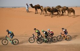 Competitors ride their bikes during Stage 5 of the 13th edition of Titan Desert 2018 mountain biking race around Merzouga in Morocco on May 3, 2018. The Titan Desert 2018 is 600 kilometre mountain bike race completed over six days, snaking between Boumalne Dades, at the foot-slopes of the High Atlas summits, and Erfoud, an oasis town in the Sahara Desert.