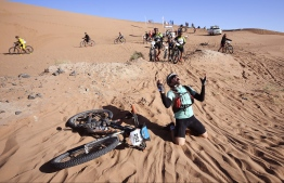 A competitor reacts after crossing a sand dune during Stage 4 of the 13th edition of the Titan Desert 2018 mountain biking race between Boumalne Dades and Merzouga in Morocco on May 2, 2018.  The Titan Desert 2018 is 600 kilometre mountain bike race completed over six days, snaking between Boumalne Dades, at the foot-slopes of the High Atlas summits, and Erfoud, an oasis town in the Sahara Desert. / AFP PHOTO / FRANCK FIFE