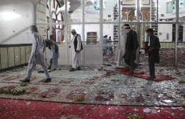 Afghan residents walk inside a damaged mosque after a suicide attack during Friday prayers in Gardez of Paktia province on August 3, 2018.  Burqa-clad suicide bombers struck a Shiite mosque in eastern Afghanistan Friday as it was crowded with worshippers for weekly prayers, killing at least 29 people and wounding more than 80 in the latest attack on the minority. / AFP PHOTO / FARID ZAHIR