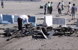 A policeman inspects the wreckage of a car bomb which exploded in front of a police station in the city of Chabahar, on December 06, 2018 in southern Iran. - A suicide bomber killed at least two people outside the police headquarters in the port city of Chabahar in restive southeastern Iran, according to a revised official toll. (Photo by STR / TASNIM NEWS / AFP)