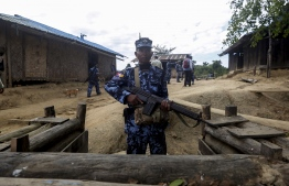 """A Myanmar border guard policeman gurads a police station in Buthidaung on January 7, 2019. - Myanmar has called on its military to """"launch operations"""" against ethnic Rakhine rebels behind a deadly attack on four police stations last week, a government spokesman said on January 7, as a surge of violence grips the restive western state. (Photo by - / AFP)"""