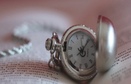 A pocket watch rests on an open book. PHOTO/sternenfern