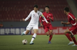 This handout photo taken on October 15, 2019 by the Korea Football Association (KFA) shows South Korea's Son Heung-min (L) and North Korea's Han Kwang Song (C) fighting for the ball during the World Cup 2022 Qualifying Asian zone Group H football match between South Korea and North Korea at Kim Il Sung Stadium in Pyongyang. North and South Korea drew 0-0 in a historic but surreal World Cup qualifier on October 15, played in front of an empty stadium and almost completely blocked off from the outside world. handout / Korea Football Association / AFP