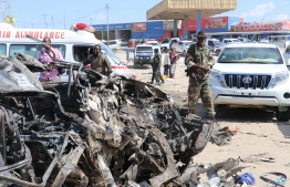 A soldier is seen next to the wreckage of car that was damaged during the car bomb that exploded in Mogadishu that killed more than 20 people is photographed in Mogadishu on December 28, 2019. - A massive car bomb exploded in a busy area of the Somali capital Mogadishu on December 28, 2019, leaving more than 20 people dead. (Photo by Abdirazak Hussein FARAH / AFP)