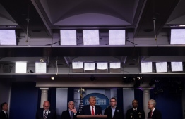 US President Donald Trump (C), flanked by (from L) CDD Director Dr. Robert Redfield, US Vice President Mike Pence, FEMA Administrator Peter Gaynor US Surgeon General Jerome Adams, and White House Trade and Manufacturing Policy Director Peter Navarro, speaks during the daily briefing on the novel coronavirus, COVID-19, at the White House on March 22, 2020, in Washington, DC. (Photo by Eric BARADAT / AFP)